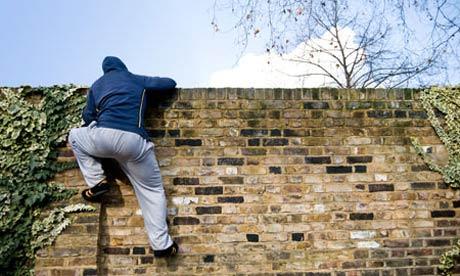 Man climbing over a wall